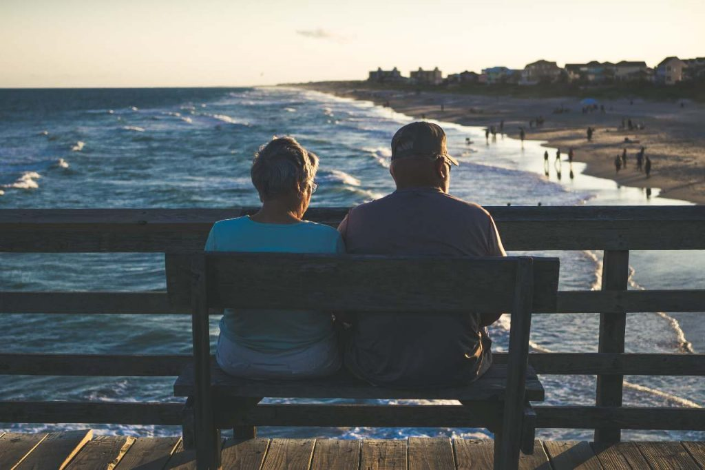 Retirement - man and woman on bench staring at the sea